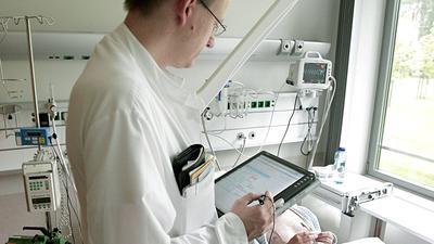 """Ein Oberarzt führt mit einem Tablet PC eine """"Laptop-Visite"""" durch."""