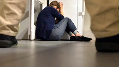 Eine Frau versucht, sich vor der Gewalt eines Mannes zu schützen.