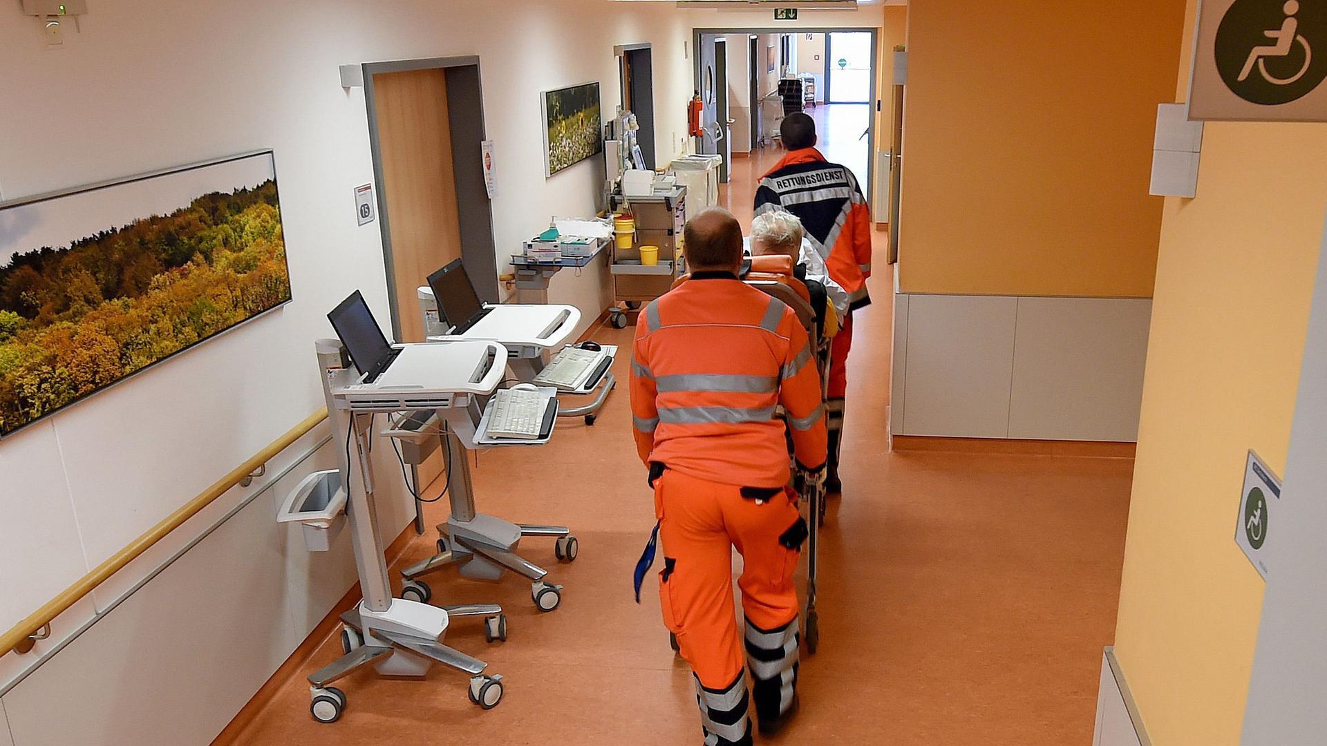 Mitarbeiter eines Rettungsdienstes schieben eine Trage mit Person über einen Flur in der Notaufnahme-Station im Klinikum.
