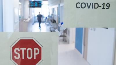 Eine Frau geht durch eine Corona-Intensivstation.