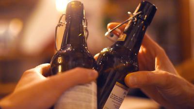 Zwei Personen stoßen in einer Kneipe mit Bier an.