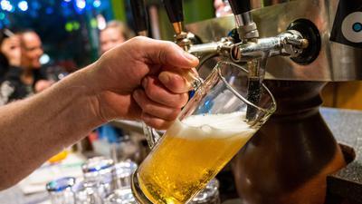 In einer Bar wird ein Bier gezapft.