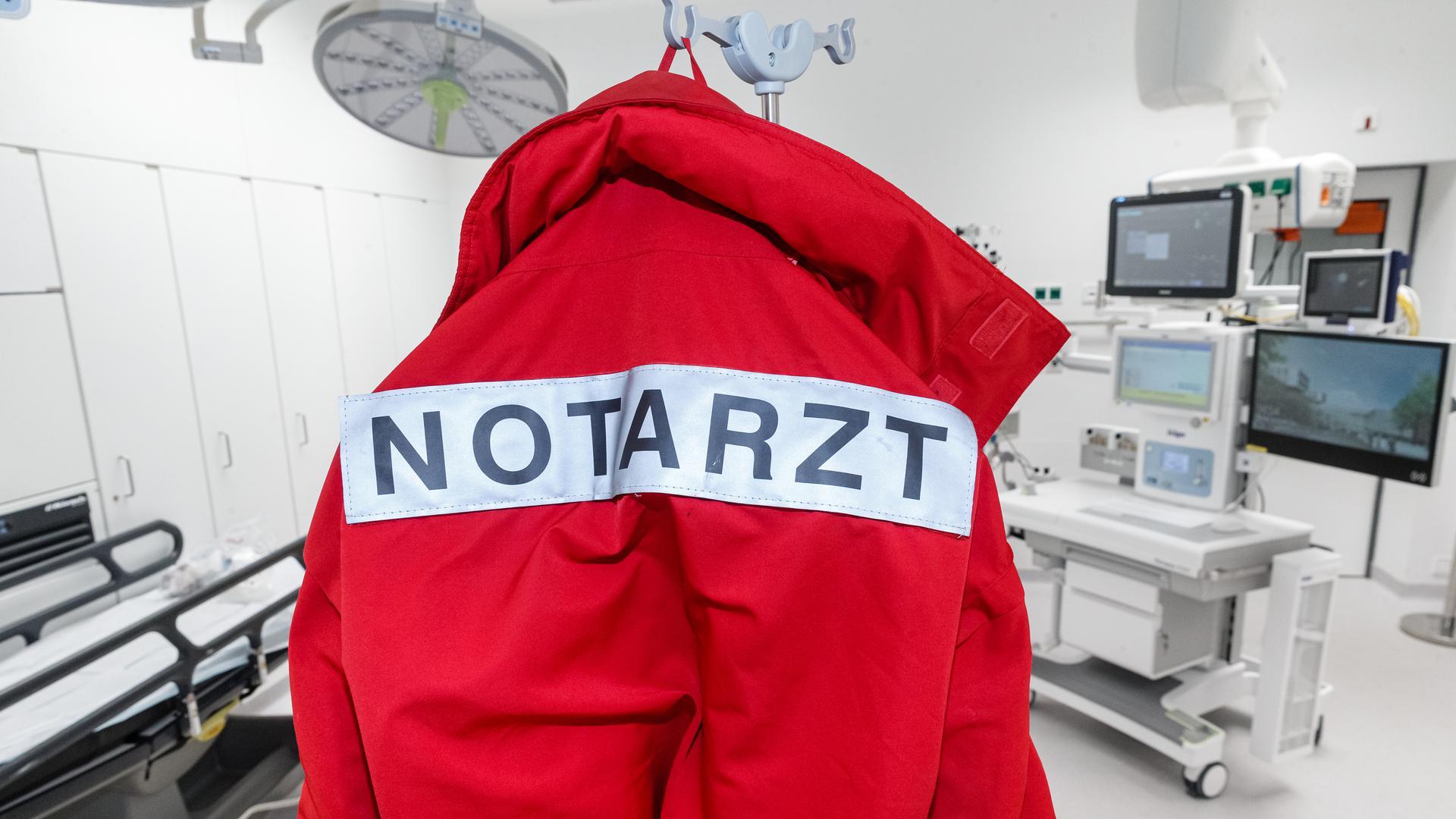 """Eine rote Jacke mit der Aufschrift """"Notarzt"""" auf dem Rücken hängt im Schockraum."""