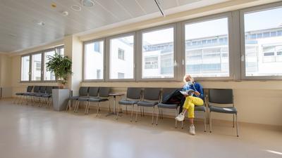 Eine Patientin mit Mundschutz wartet in einem ansonsten leeren Wartebereich.