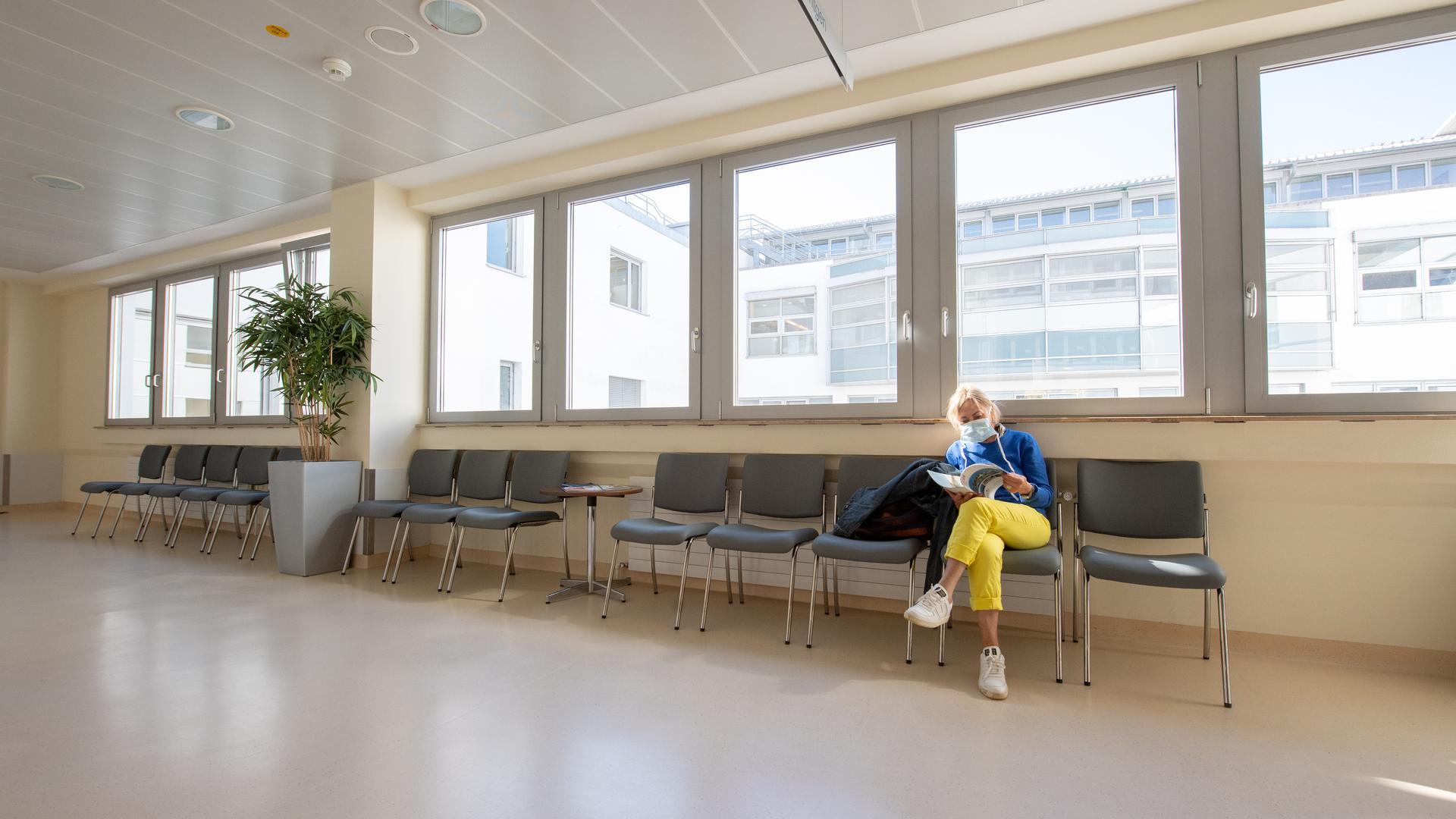 Eine Patientin mit Mundschutz wartet in einem ansonsten leeren Wartebereich in einer Klinik in Gauting bei München. Die Corona-Krise lässt deutschlandweit die Umsätze der Krankenhäuser schrumpfen. Manche Kliniken fürchten Zahlungsschwierigkeiten. +++ dpa-Bildfunk +++