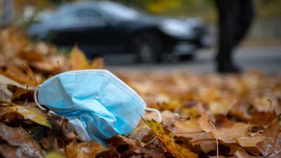 Eine Gesichtsmaske liegt am Straßennrand.