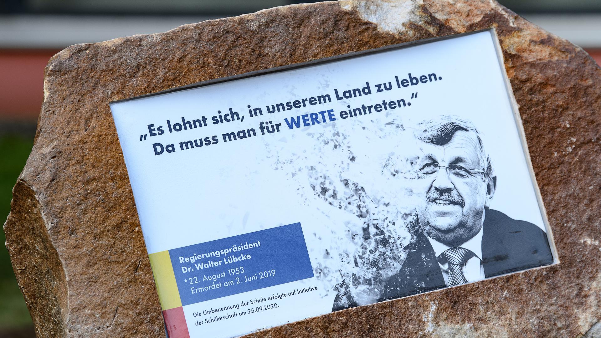 """Ein Gedenkstein mit der Aufschrift """"Es lohnt sich, in unserem Land zu leben. Da muss man für WERTE eintreten"""" liegt vor der Walter-Lübcke-Schule."""