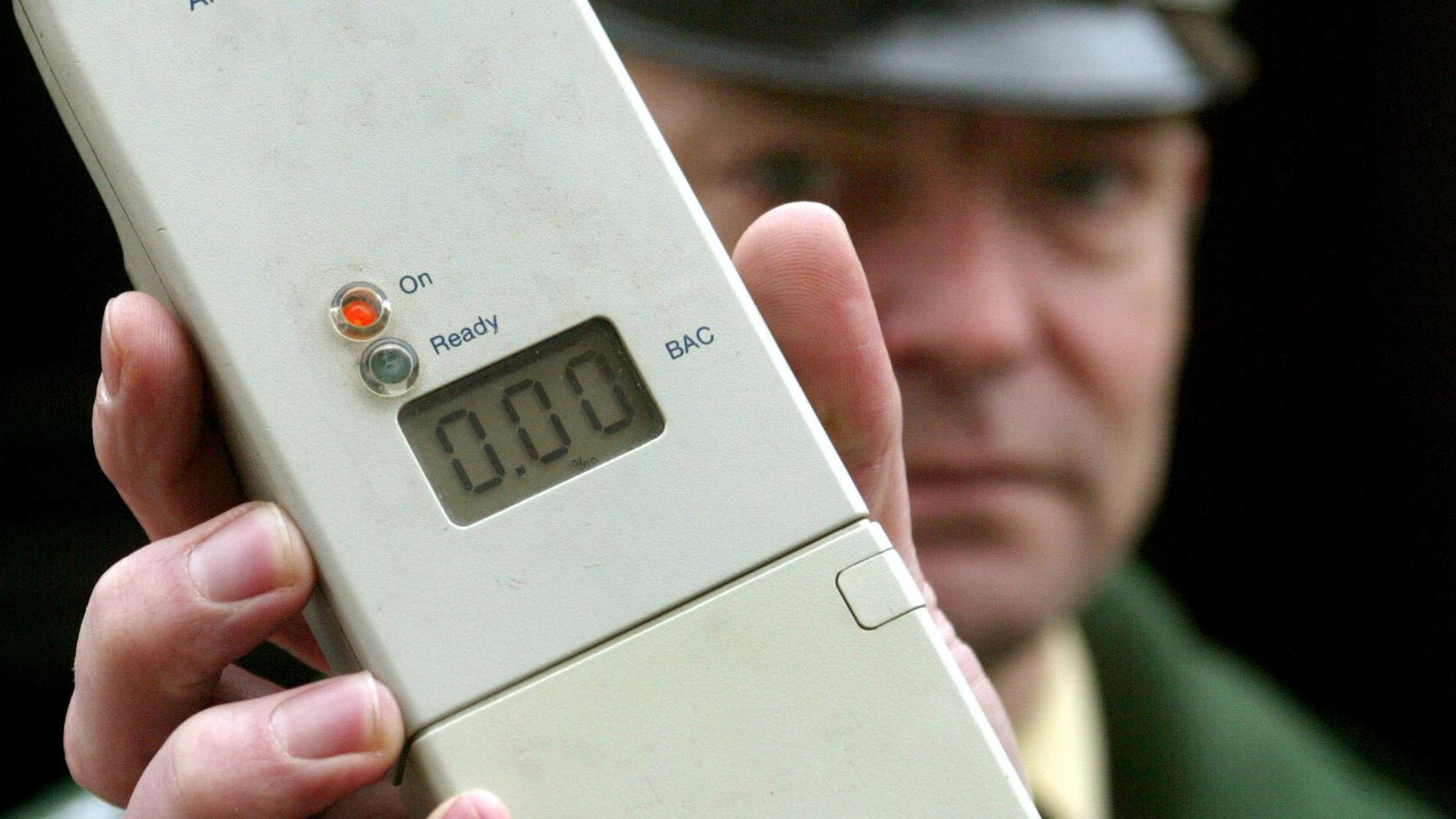 ARCHIV - Ein Polizist zeigt in Magdeburg ein Alkohol-Atemmessgerät (Archivfoto vom 08.03.2005). Beim 47. Verkehrsgerichtstag, der am kommenden Donnerstag (29.01.2009) in Goslar beginnt, werden sich die Fachleute über das Dauerbrenner-Thema Promillegrenze wieder einmal die Köpfe heißreden. Dabei geht es vor allem darum, wie der Alkohol-Pegel von Autofahrern am genauesten und am schnellsten gemessen werden kann. Angeheizt wird die Debatte durch einen Vorschlag der Bundes-Drogenbeauftragten Bätzing, die für eine Senkung der Promille-Grenze auf 0,3 Prozent plädiert. Foto: Jens Wolf/lah/lni (zu lni 0420) +++(c) dpa - Bildfunk+++ sdwsa