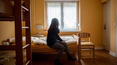 Eine Frau sitzt am 12.11.2015 im Frauenhaus in Herne (Nordrhein-Westfalen) auf einem Bett. Foto: Maja Hitij/dpa (zu lnw-KORR vom 23.11.2015) +++(c) dpa - Bildfunk+++ | Verwendung weltweit