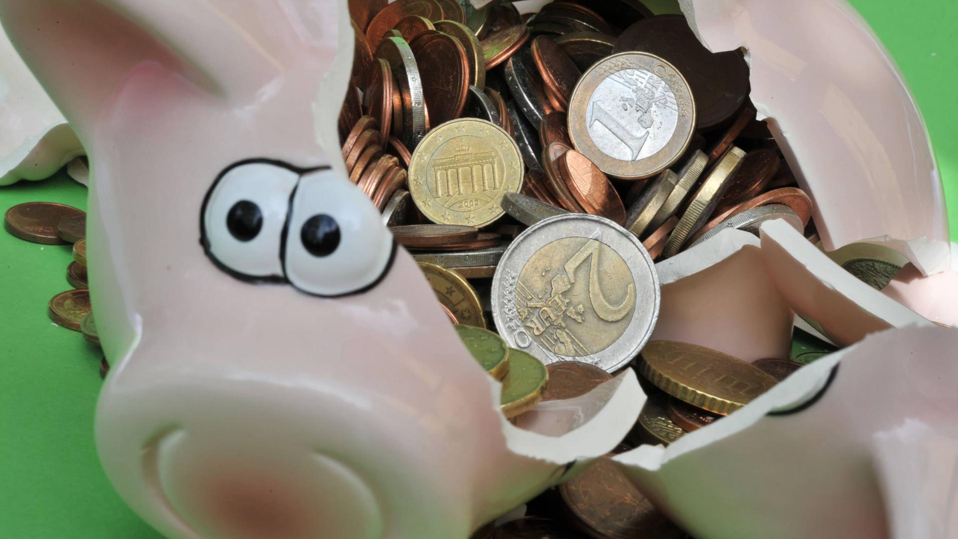 """ARCHIV - 10.06.2010, Bayern, München: ILLUSTRATION - Ein Sparschwein mit Euro-Geldstücken liegt zerbrochen auf einem Tisch. (zu dpa:""""Sparer in Deutschland haben vor allem Altersvorsorge im Blick"""" Foto: Peter Kneffel/dpa +++ dpa-Bildfunk +++   Verwendung weltweit"""