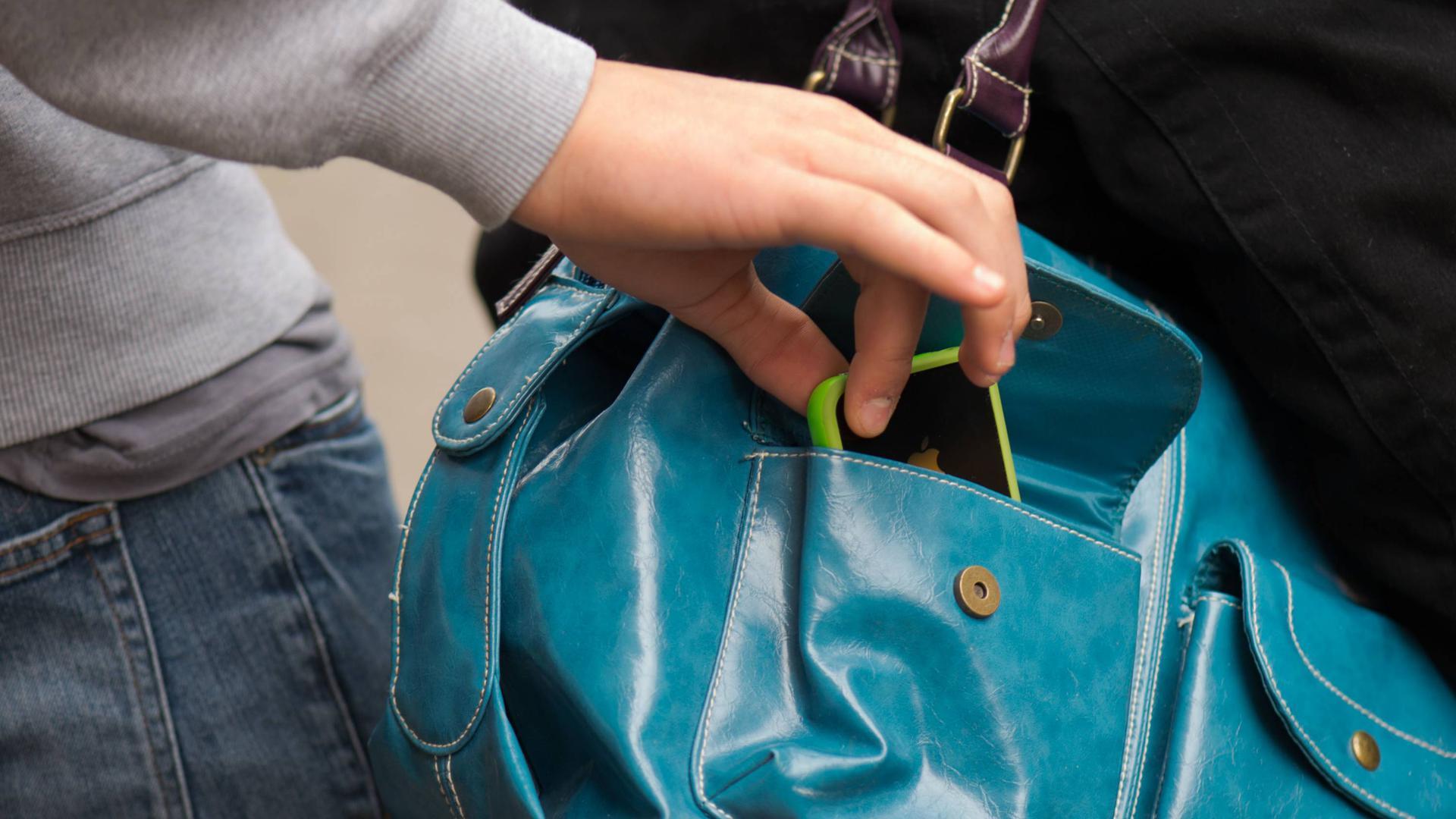 """ARCHIV - ILLUSTRATION - Ein Mann stiehlt am 21.08.2014 einer Frau an einer Bus- und Straßenbahnhaltestelle in Dresden (Sachsen) ein Smartphone aus einer Handtasche (gestellte Szene).  Foto: Arno Burgi/dpa (zu dpa """"Schnäppchen im Schlussverkauf locken auch Taschendiebe an"""" vom 06.08.2016) +++(c) dpa - Bildfunk+++   Verwendung weltweit"""