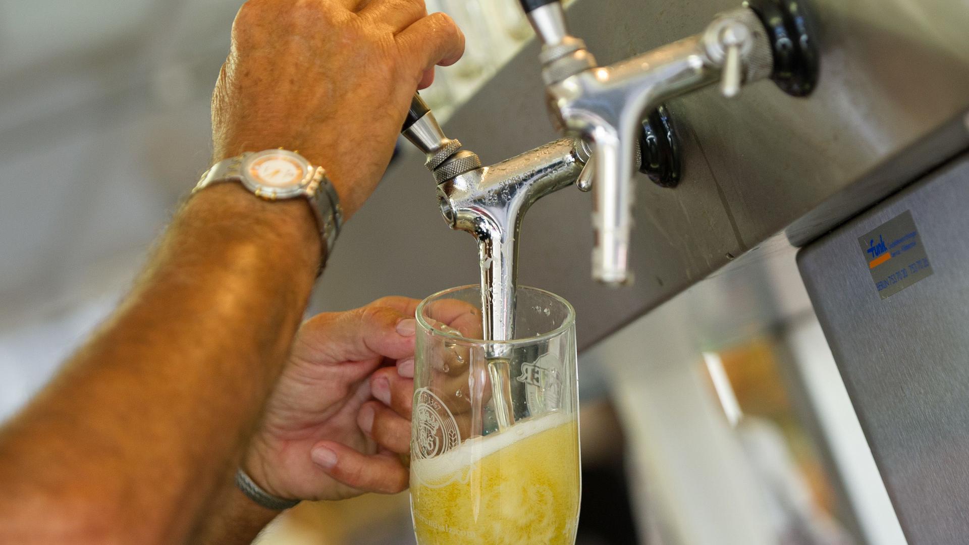 Ein Mann zapft ein Bier.