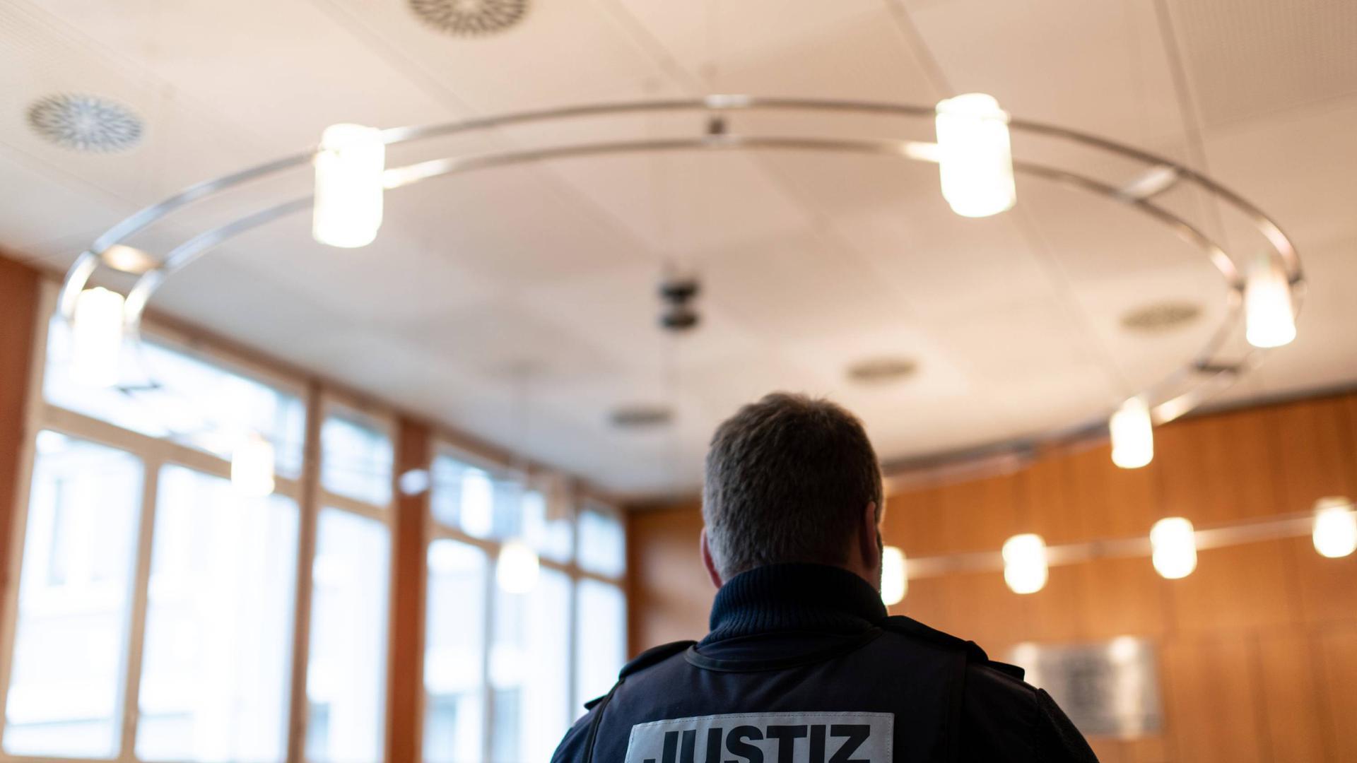 30.01.2019, Baden-Württemberg, Offenburg: Ein Justizbeamter steht vor Prozessbeginn im Landgericht. Vor Gericht steht ein 27-jähriger Somalier. Dem Asylbewerber aus Somalia wird vorgeworfen, im August 2018 einen Arzt in dessen Praxis in Offenburg mit einem Messer getötet und eine Arzthelferin verletzt zu haben. Foto: Patrick Seeger/dpa - ACHTUNG: Person(en) wurde(n) aus rechtlichen Gründen gepixelt +++ dpa-Bildfunk +++ | Verwendung weltweit