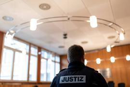 30.01.2019, Baden-Württemberg, Offenburg: Ein Justizbeamter steht vor Prozessbeginn im Landgericht. Vor Gericht steht ein 27-jähriger Somalier. Dem Asylbewerber aus Somalia wird vorgeworfen, im August 2018 einen Arzt in dessen Praxis in Offenburg mit einem Messer getötet und eine Arzthelferin verletzt zu haben. Foto: Patrick Seeger/dpa - ACHTUNG: Person(en) wurde(n) aus rechtlichen Gründen gepixelt +++ dpa-Bildfunk +++   Verwendung weltweit