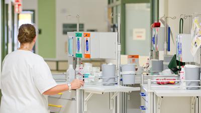 Eine Krankenpflegerin steht im Flur ihrer Station an einem Pflegewagen.