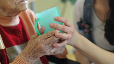 Eine Pflegekraft hilft einer alten Frau beim Trinken aus einem Becher in einem Seniorenheim.