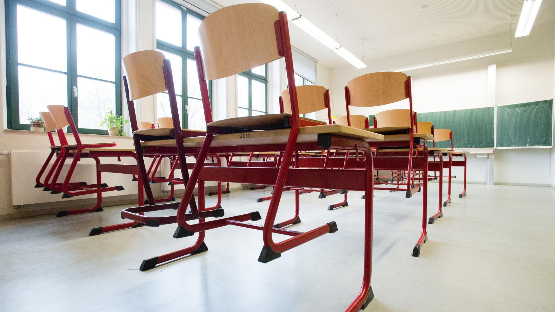 Stühle stehen auf Tischen in einem leeren Klassenzimmer einer Schule.
