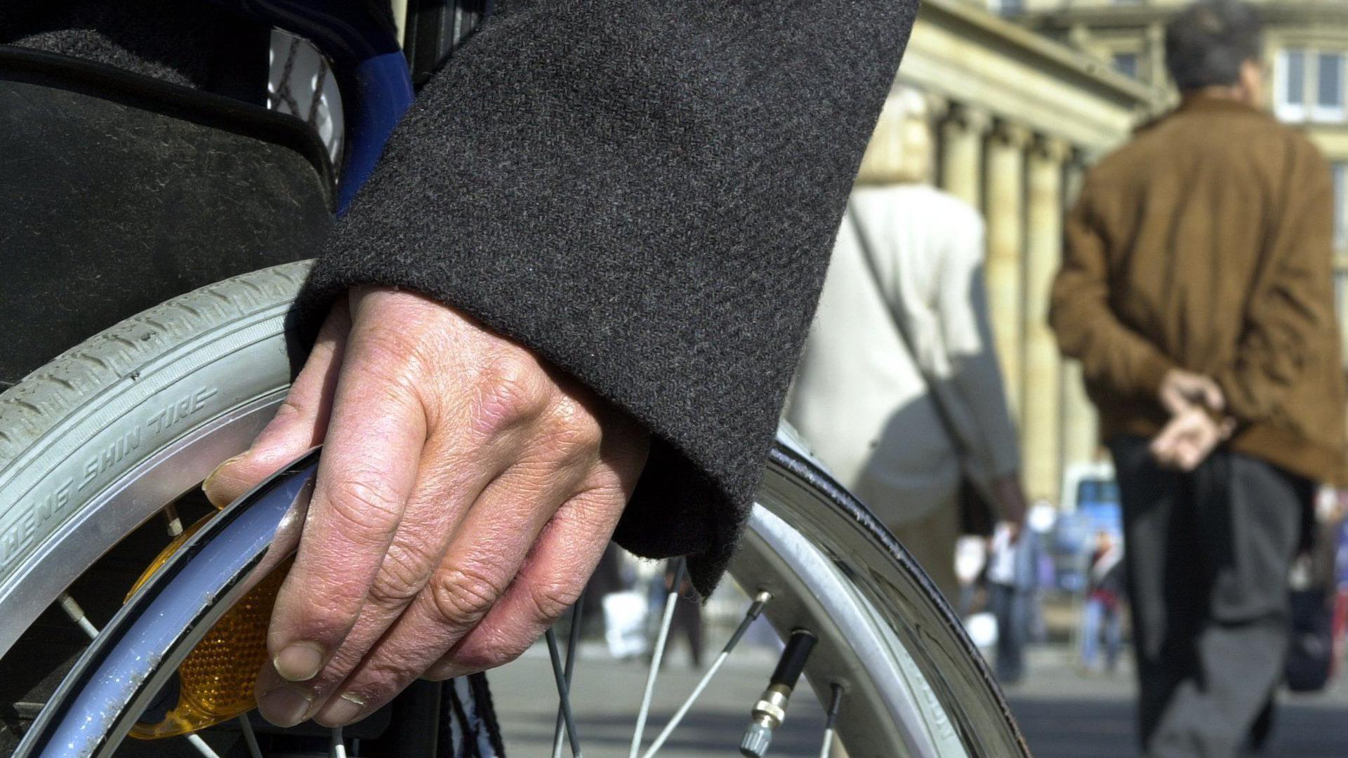 Die Hand eines Rollstuhlfahrers liegt auf dem Rad des Stuhls