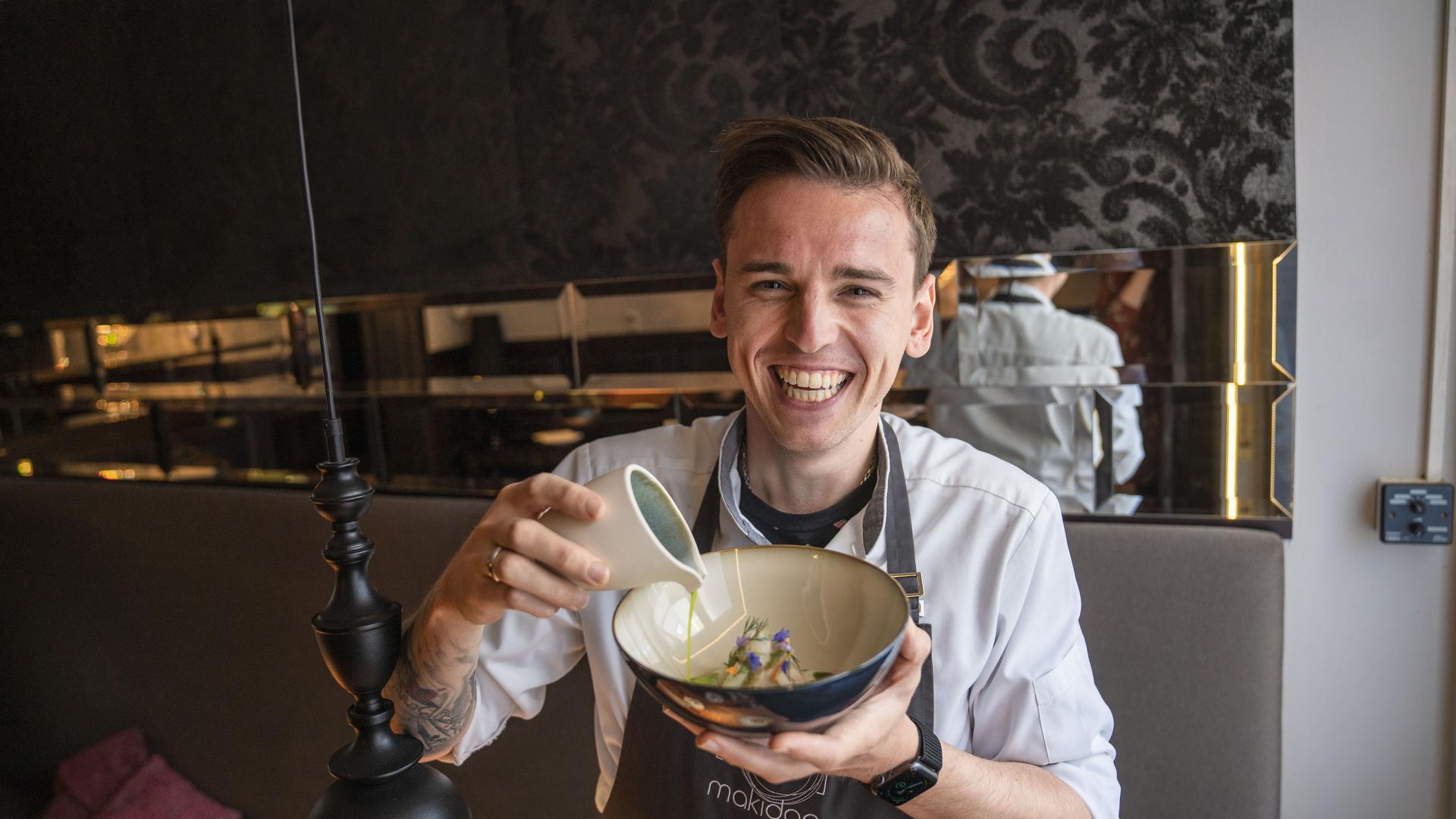 Daniel Weimer schüttet fermentierten Kohlrabisaft in einen Teller und lacht sich kaputt.