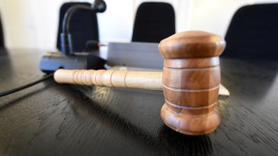 Auf der Richterbank im Schwurgerichtssaal liegt ein Richterhammer aus Holz.