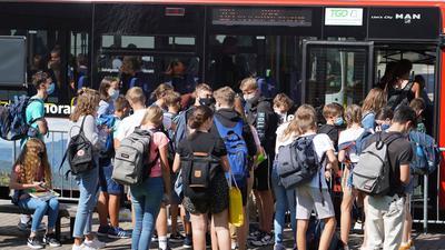 Jugendliche vor einem Schulbus