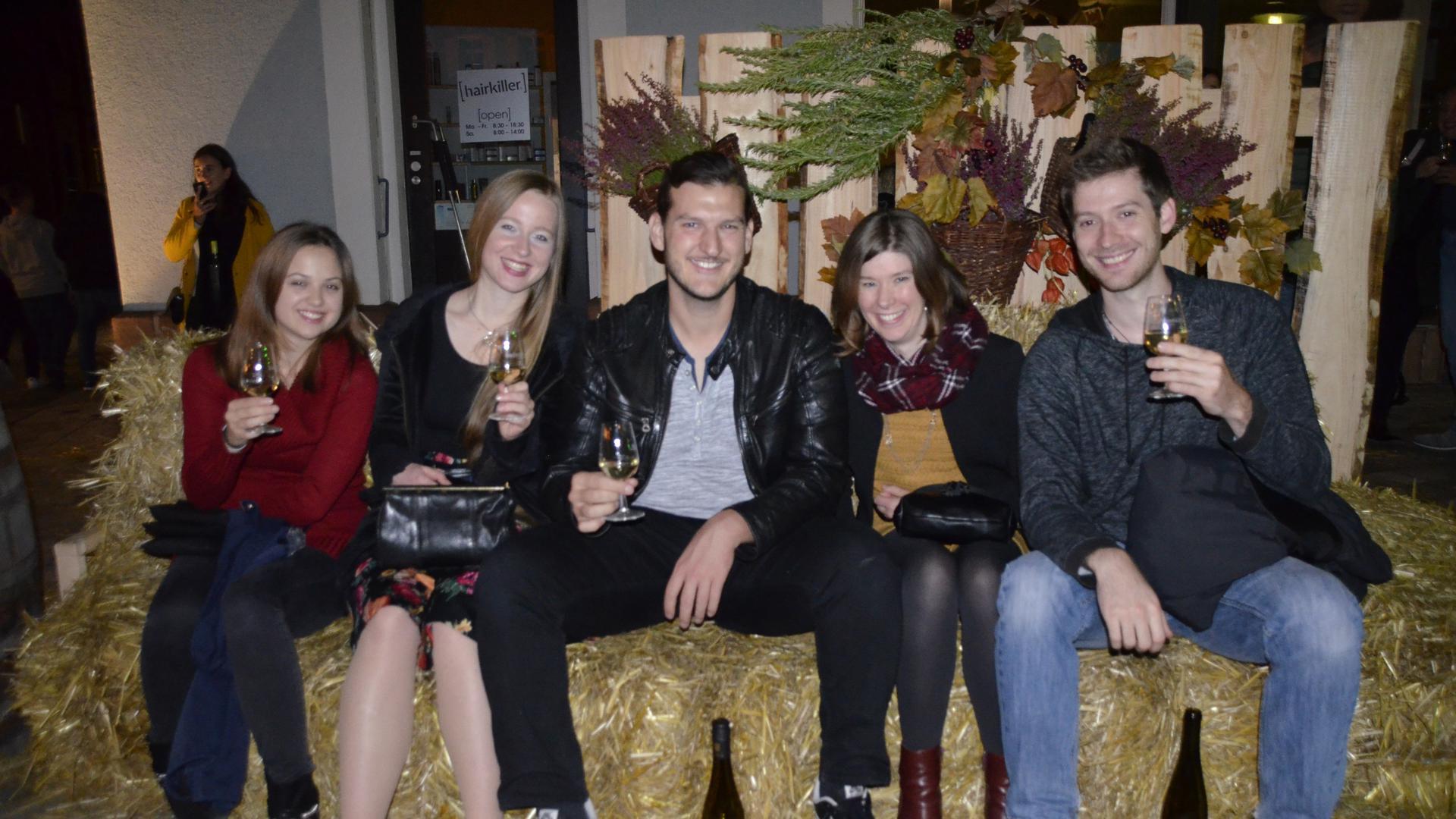 Mehrere Personen mit Weingläsern sitzen auf Heuballen und prosten in die Kamera.