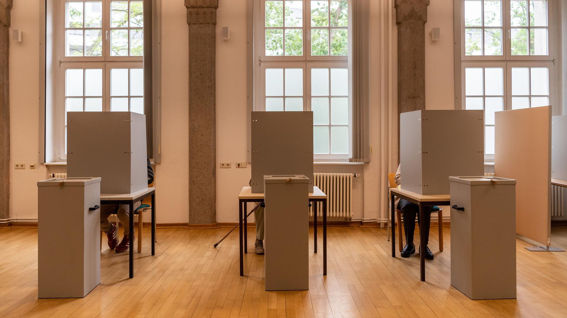 Bürger sitzen im Wahllokal für die Briefwahl in Wahlkabinen.