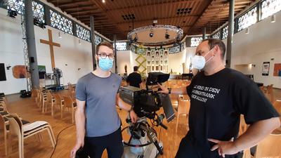 David Falk (links) von der Kirchengemeinde unterhält sich mit einem Kameramann