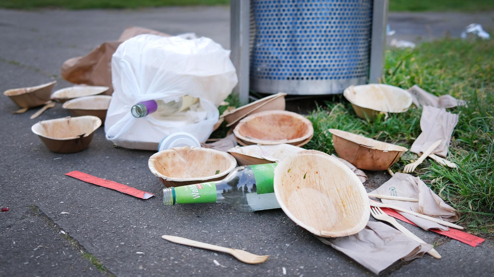 Einweggeschirr liegt neben einem vollen Mülleimer an einem Park in Düsseldorf. Wegen der Corona-Krise nimmt das Abfallaufkommen zu. +++ dpa-Bildfunk +++