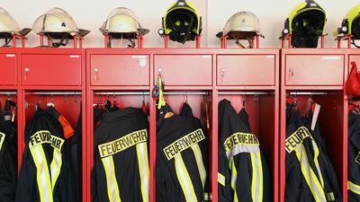 Ein Schrank mit Jacken und Helmen der Freiwilligen Feuerwehr steht in einem Gebäude.