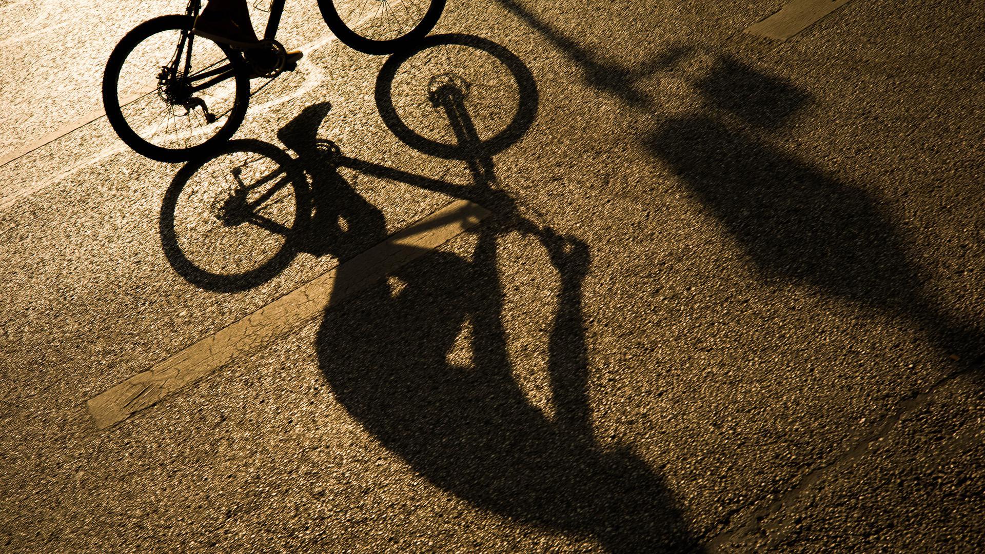 Der Schatten eines Radfahrers zeichnet sich in Licht der Abendsonne auf dem Asphalt einer Strasse in der Innenstadt ab. (zu dpa «Umfrage: Viele Bürger wollen auch nach Corona mehr mit dem Rad fahren»)