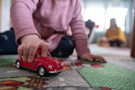 Ein Kind, das normalerweise im Kindergarten wäre, spielt zu Hause. Im Hintergrund sitzt die Mutter des Kindes. Am 1. Februar 2021 sollen nach Willen der Landesregierung von Baden-Württemberg Kitas und Grundschulen wahrscheinlich schrittweise wieder geöffnet werden. +++ dpa-Bildfunk +++