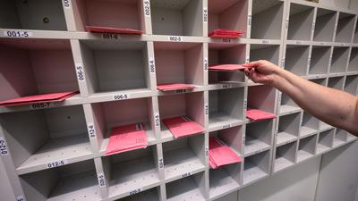 Eine Wahlhelferin legt Wahlbriefe in ein Regal.