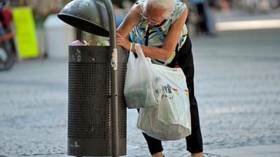 Eine alte Frau sucht in einer Mülltonne nach Pfandflaschen.