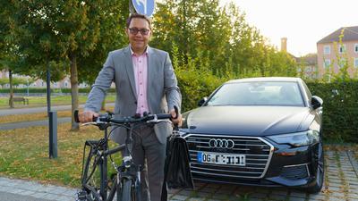 Mann mit Fahrrad vor Auto