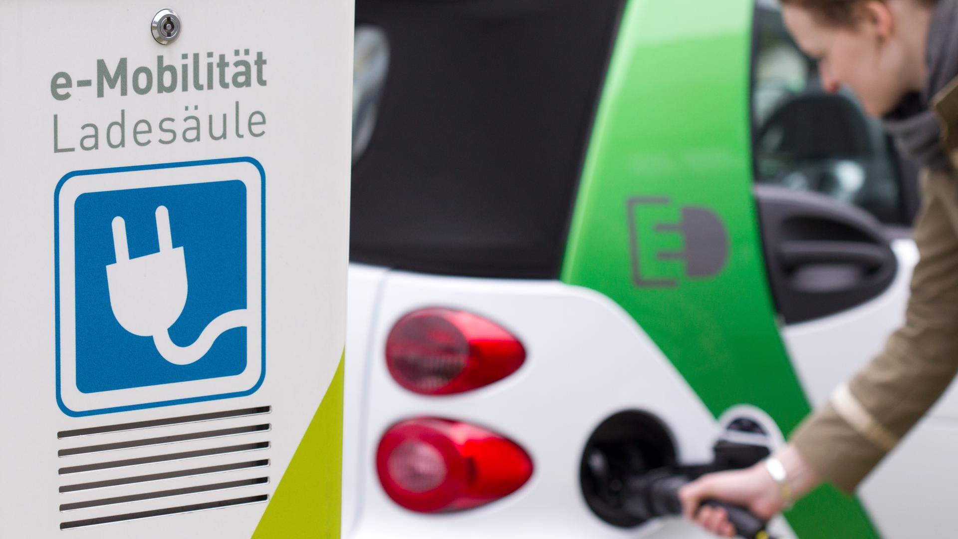 Ein Ladestecker wird ausgehend von einer e-Mobilität Ladesäule in die Ladedose eines batteriebetriebenes Fahrzeugs gesteckt.
