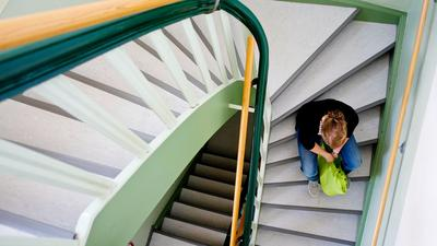 Eine junge Frau sitzt auf einer Treppe.
