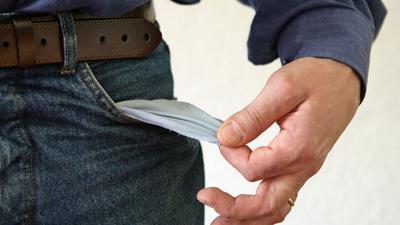 Ein Mann zeigt seine leere Hosentasche.