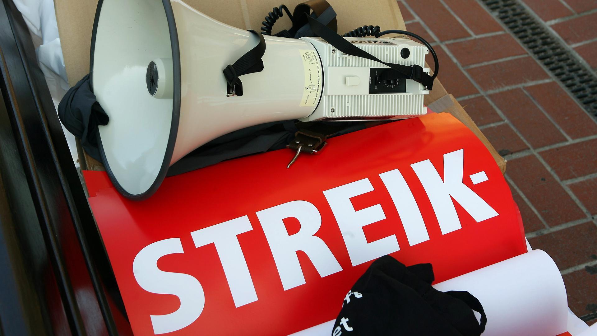 Ein Megafon und Streikplakate liegen am Rande einer Kundgebung.