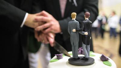 ZweiMänner schneiden eine Hochzeitstorte an.
