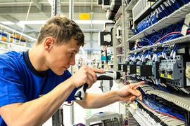 Ein Auszubildender arbeitet an Kabeln.