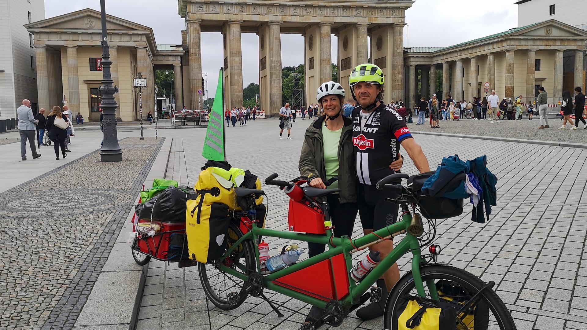 Das Ehepaar Schweizer aus Wagshurst steht it seinem Tandem vor dem Brandenburger Tor in Berlin.