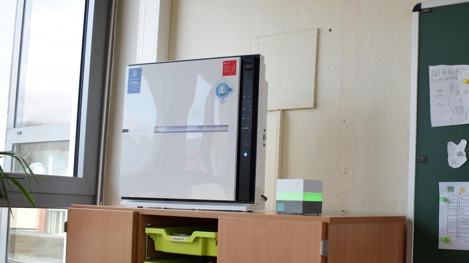 Ein Luftfilter-Gerät steht in einer Schule auf einem Schrank.