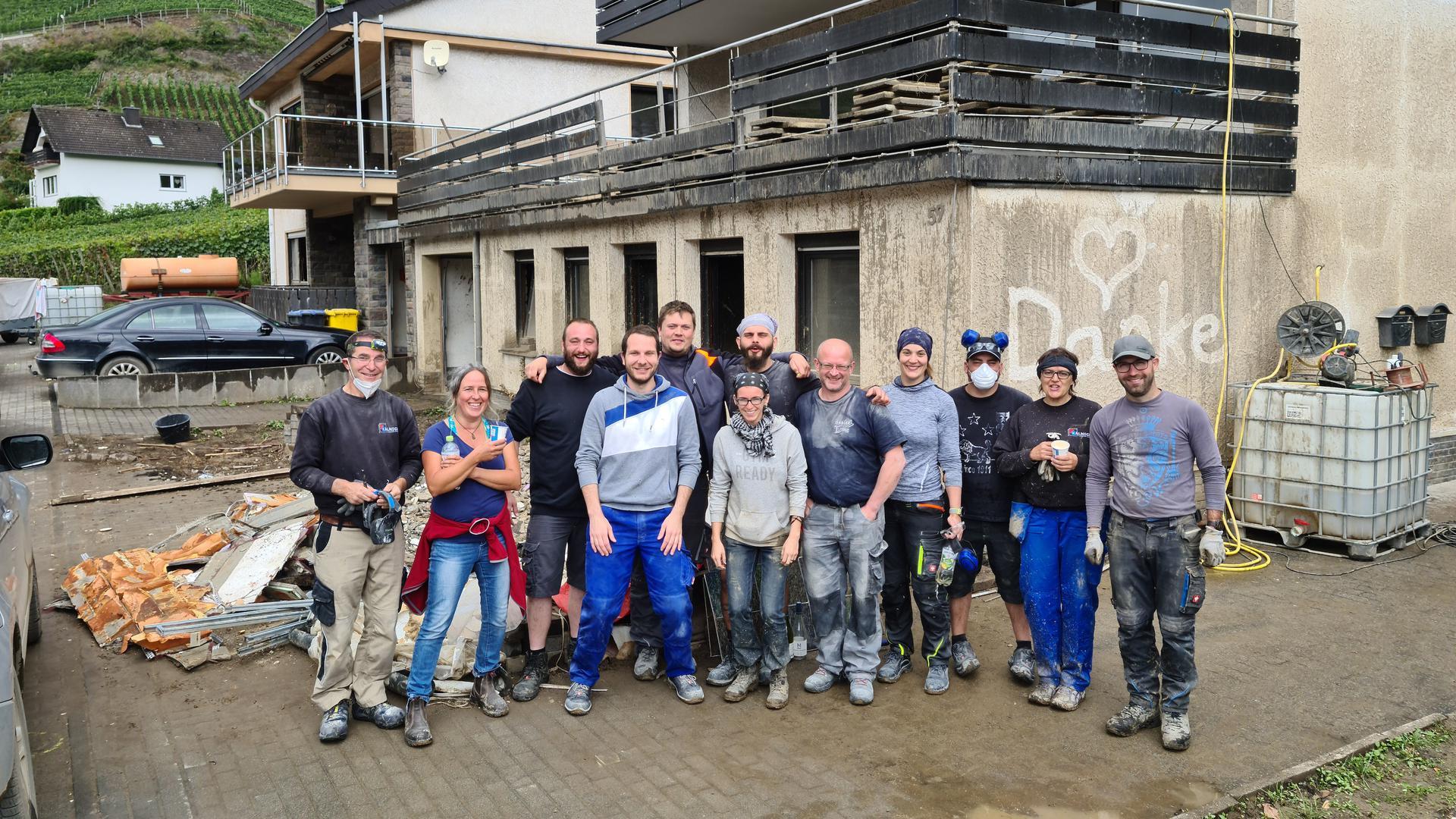 Zwölf Männer und Frauen in schmutziger Arbeitskleidung stehen vor einem dreckverschmierten Haus, auf das ein Herz und das Wort Danke gemalt wurden.