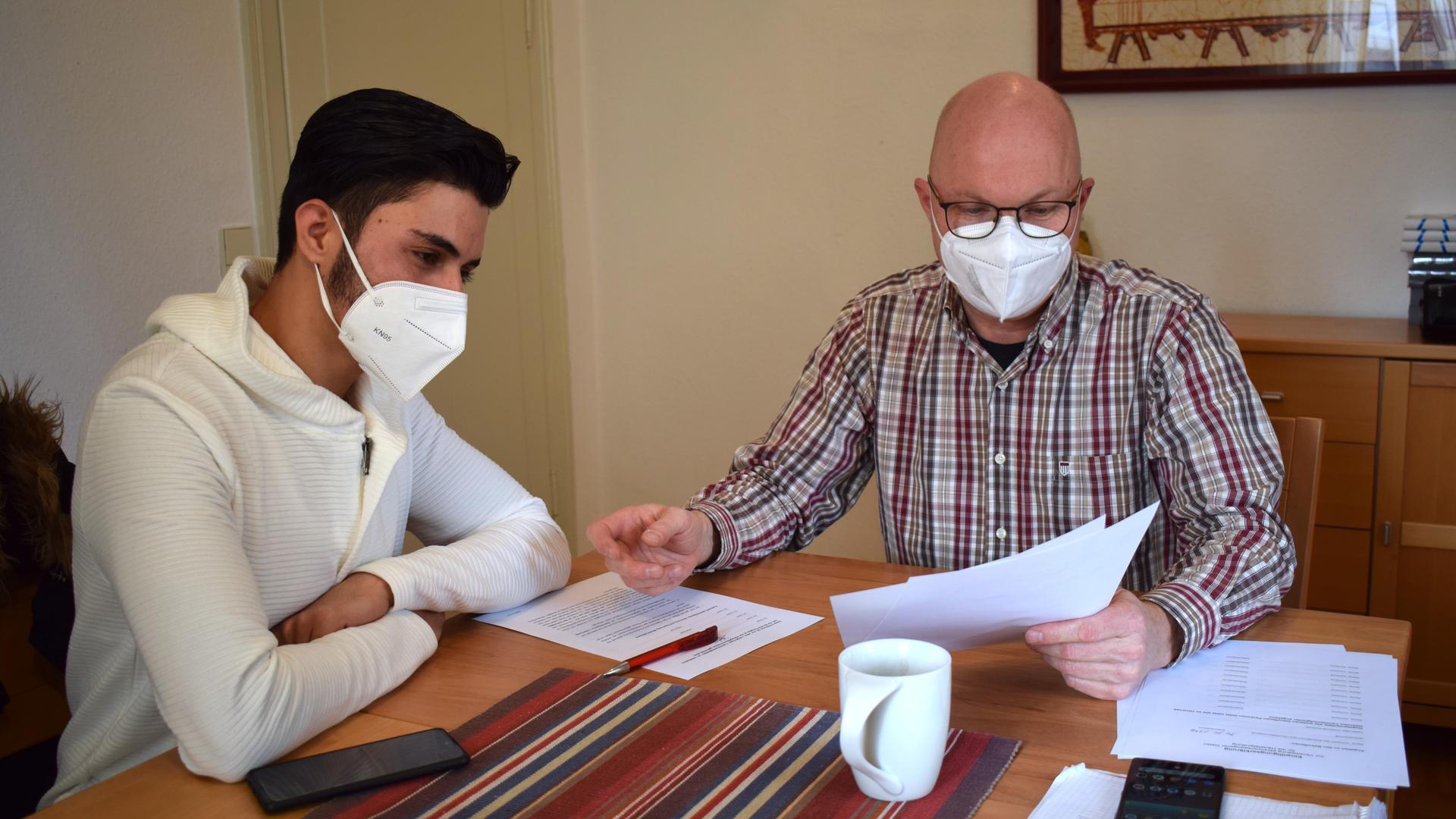 Zwei Männer sitzen mit Maske an einem Tisch und schauen sich Papiere an.
