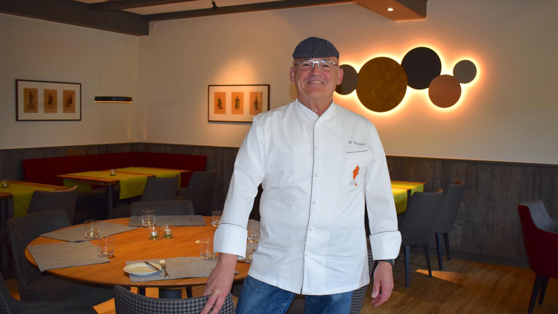 Ein strahlend lächelnder Mann mit weißer Kochjacke und dunkler Schiebermütze steht in einem modernen Gastraum.