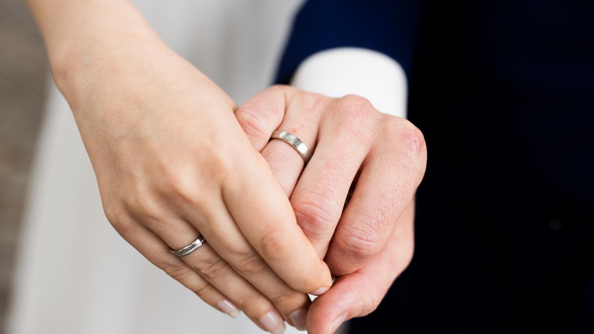 Ein Brautpaar reicht sich die Hände.