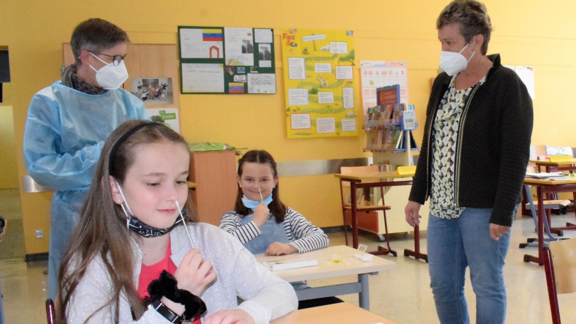 Zwei Schülerinnen sitzen in einem Klassenzimmer und führen ein Stäbchen an ihre Nase. Zwei Frauen beobachten sie dabei.