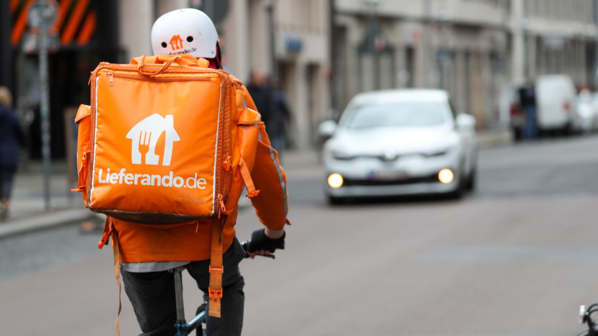"""Ein Fahradbote vom Lieferdienst """"Lieferando.de"""" fährt durch eine Innenstadt."""