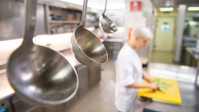 Eine Köchin in Ausbildung schneidet Lebensmittel klein.